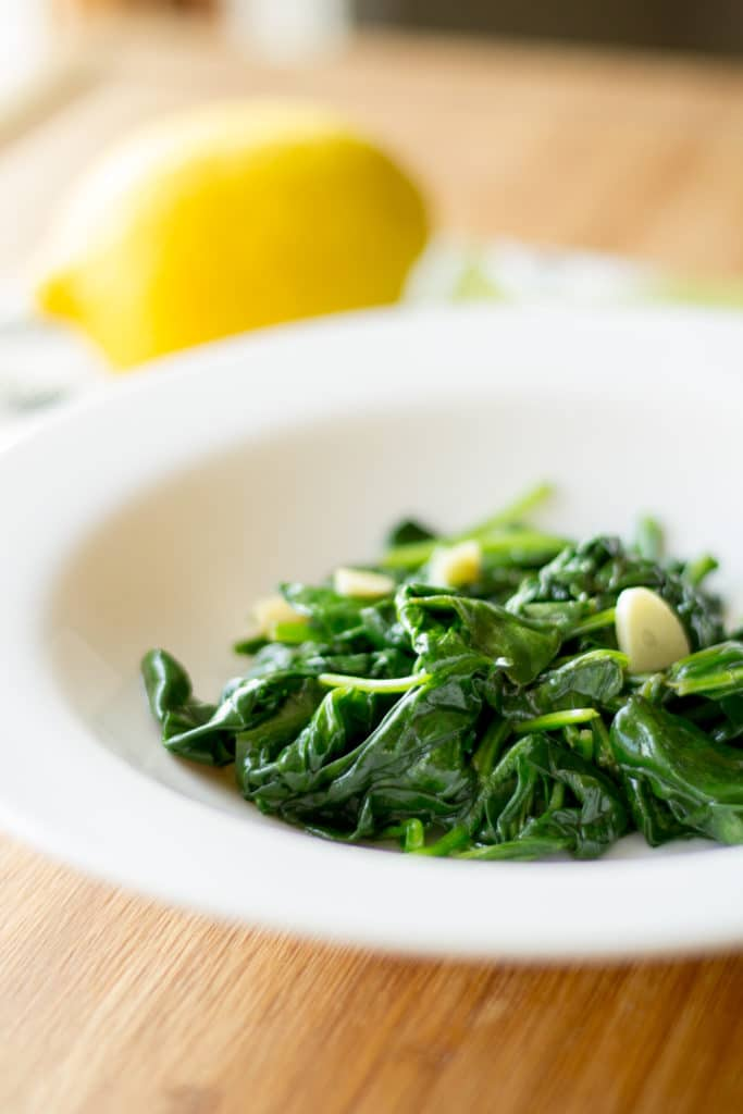 Spinach sautéed with lemon and garlic in a bowl.