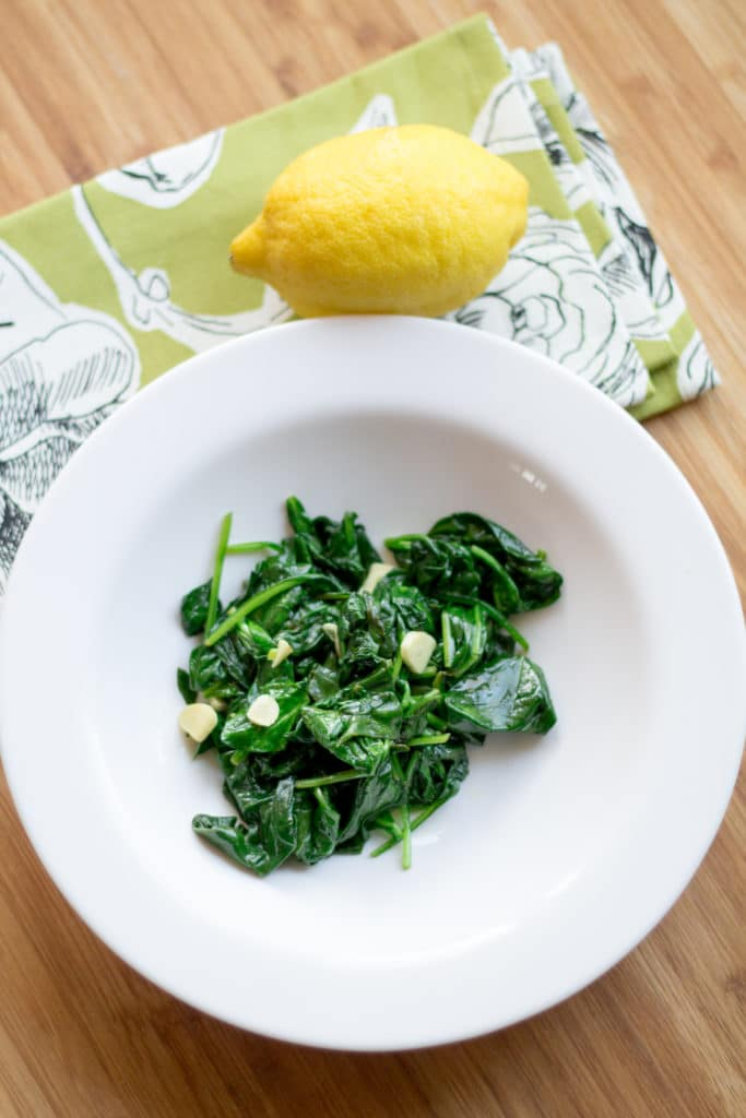 Spinach sautéed with lemon and garlic in a bowl on a table