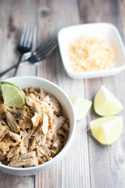 shredded chicken in a bowl next to lime wedges