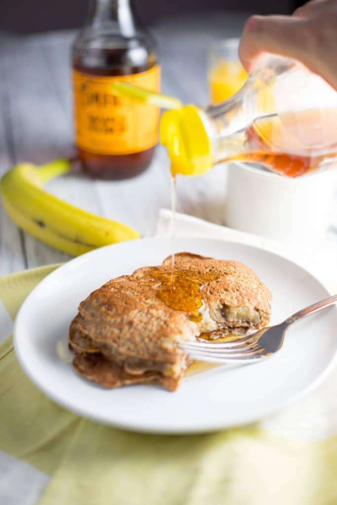 syrup pouring onto banana pancakes