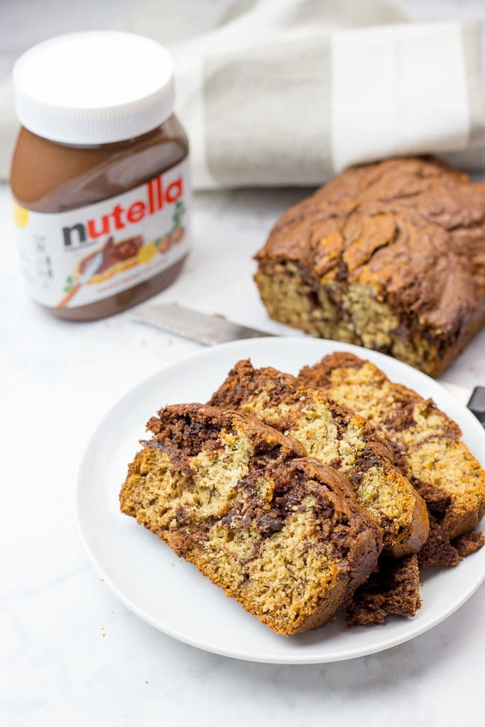a plate of banana bread with a jar of nutella next to it