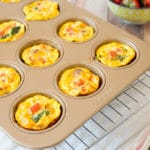 egg bake muffins in a pan next to a bowl of strawberries