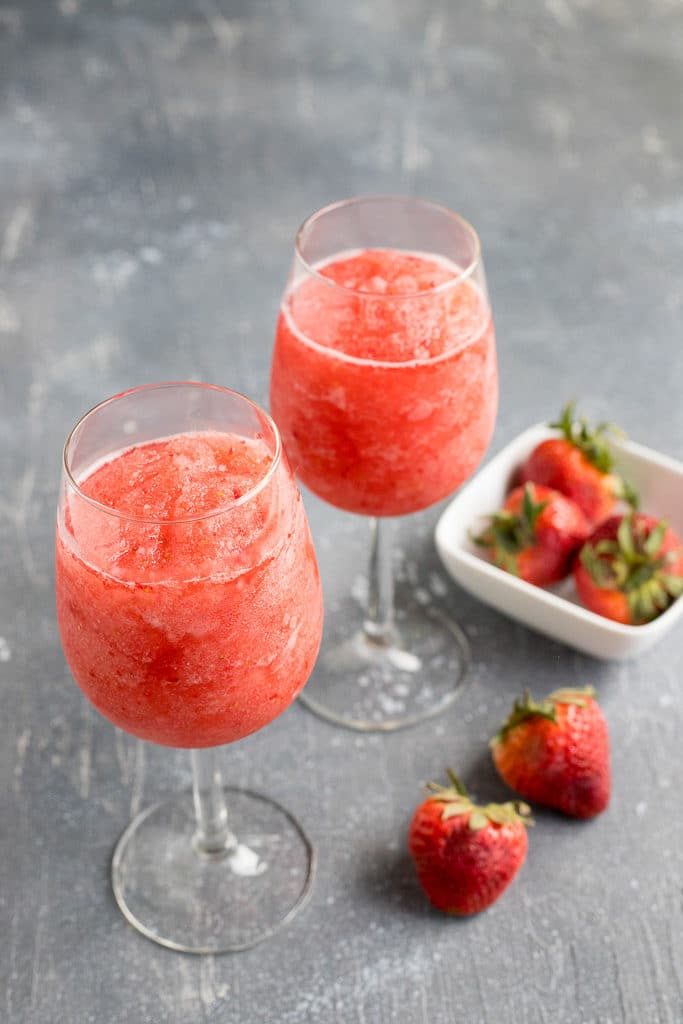 two glasses of frozen rose next to a bowl of strawberries